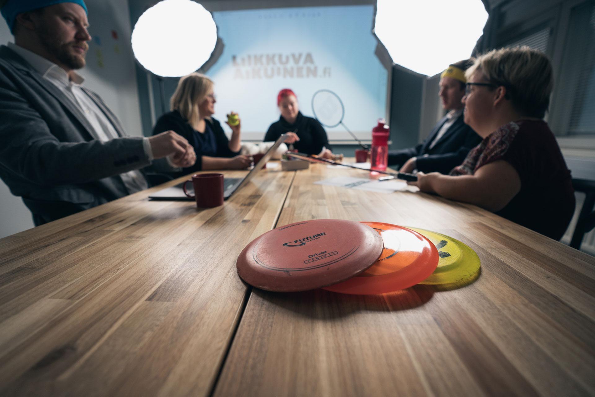 Ihmisiä istuu neuvottelupöydän ääressä.