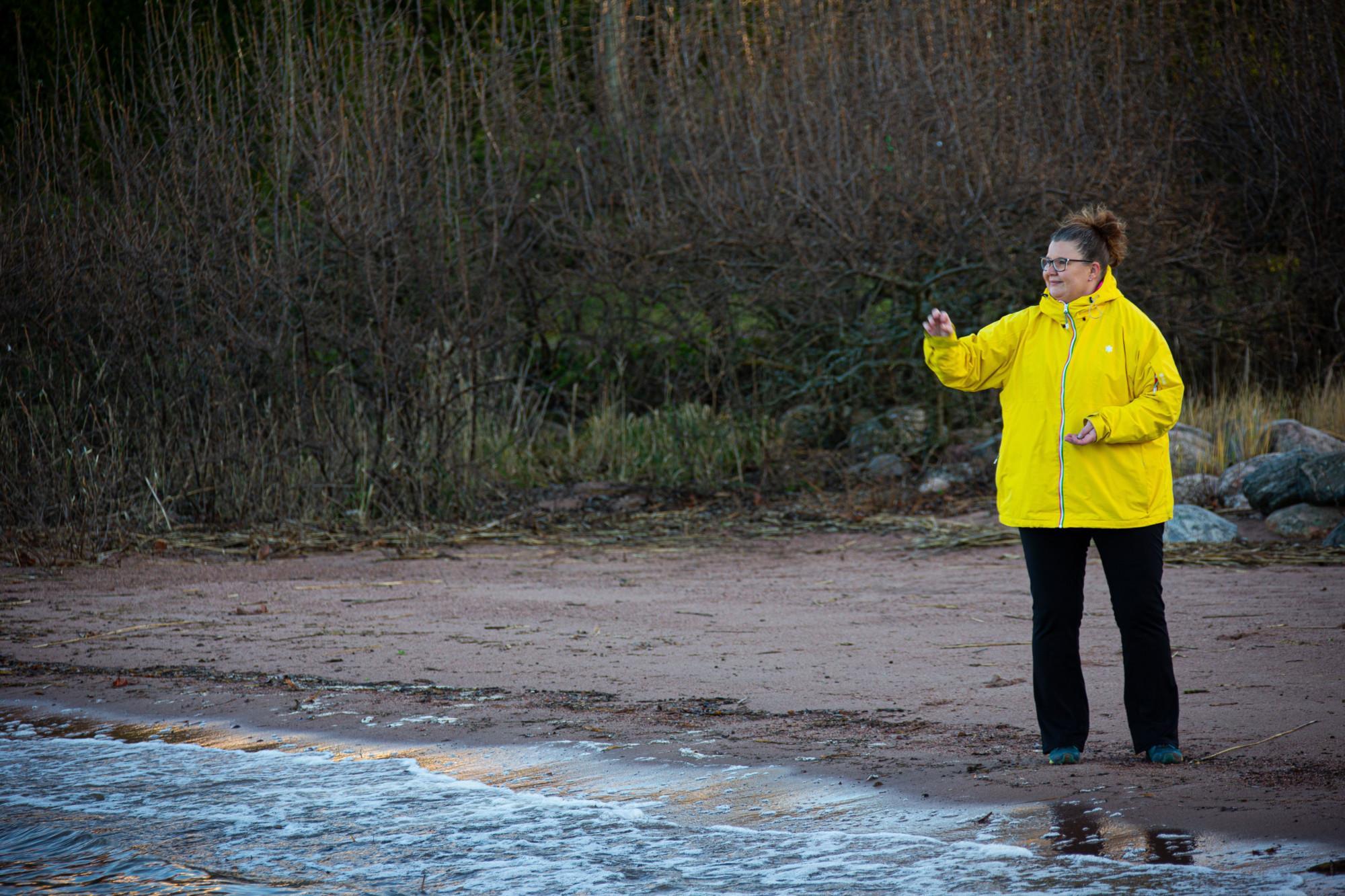 Nainen seisoo rannalla ja heittelee kiviä järveen.