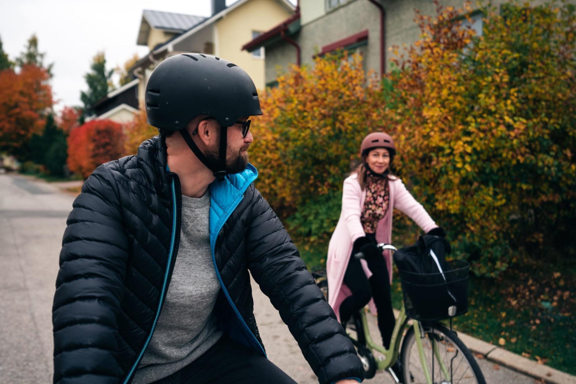 Mies ja nainen pyöräilevät taajamassa.