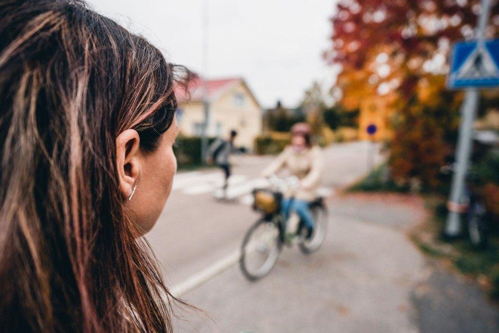 Nainen katsoo, kun pyöräilijä ja skeittaaja liikkuvat kadulla.