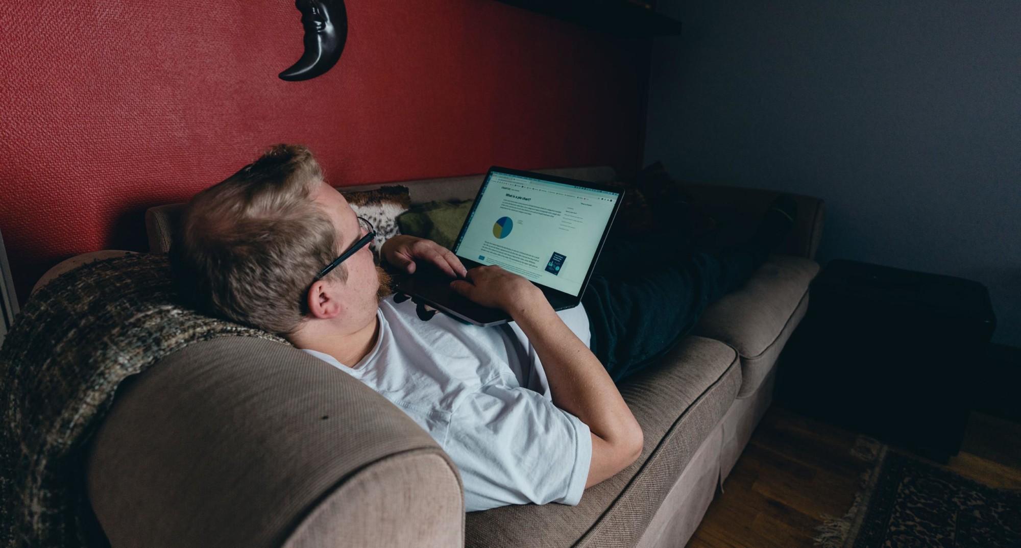 Mies makaa sohvalla ja selaa nettiä.