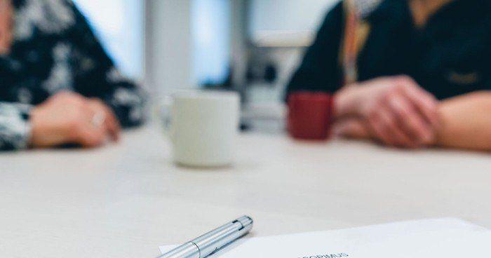 Kaksi ihmistä neuvottelupöydän ääressä. Etualalla tehdyt muistiinpanot.