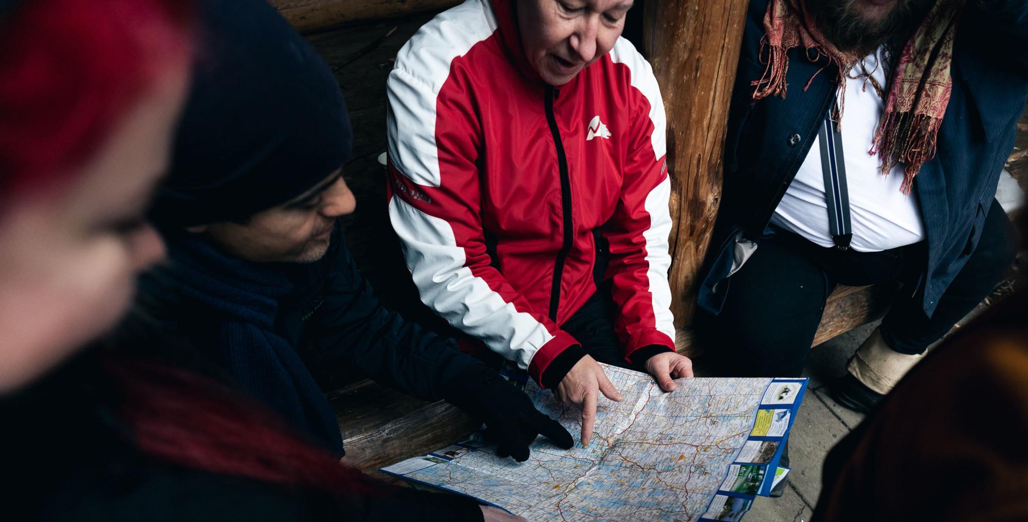 Ihmiset tutkivat karttaa luontokodalla..