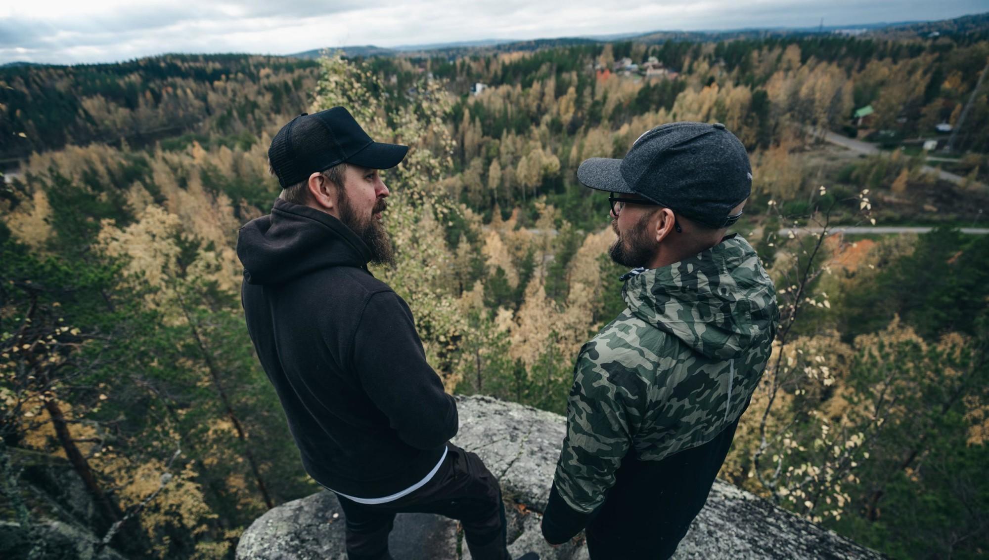 Kaksi miestä seisoo ison kallion päällä.