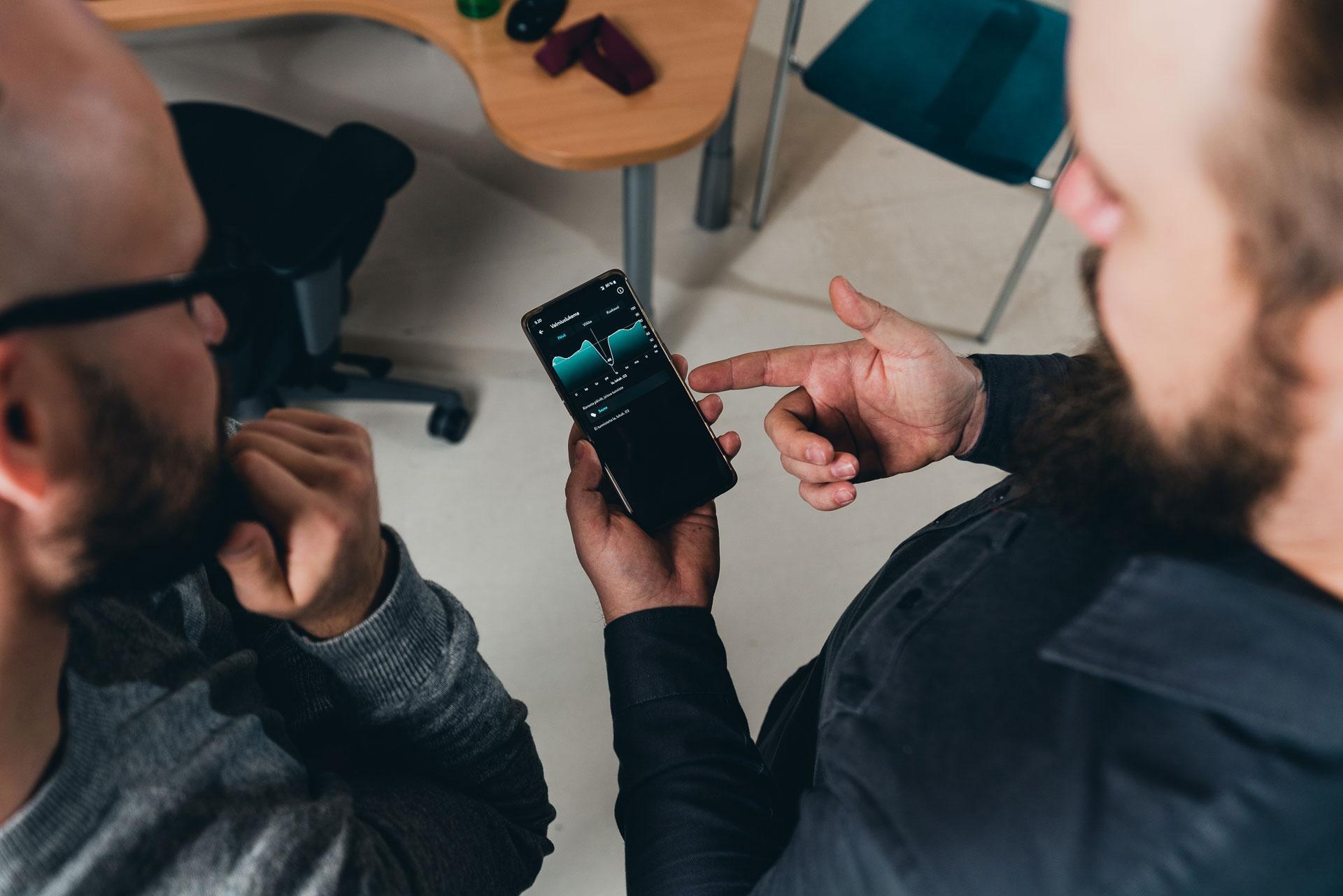 Kaksi henkilöä tutkii kännykkäsovellusta.