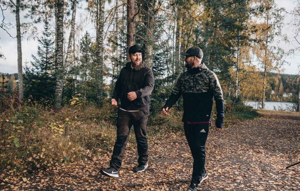 Kaksi miestä kävelee polulla.