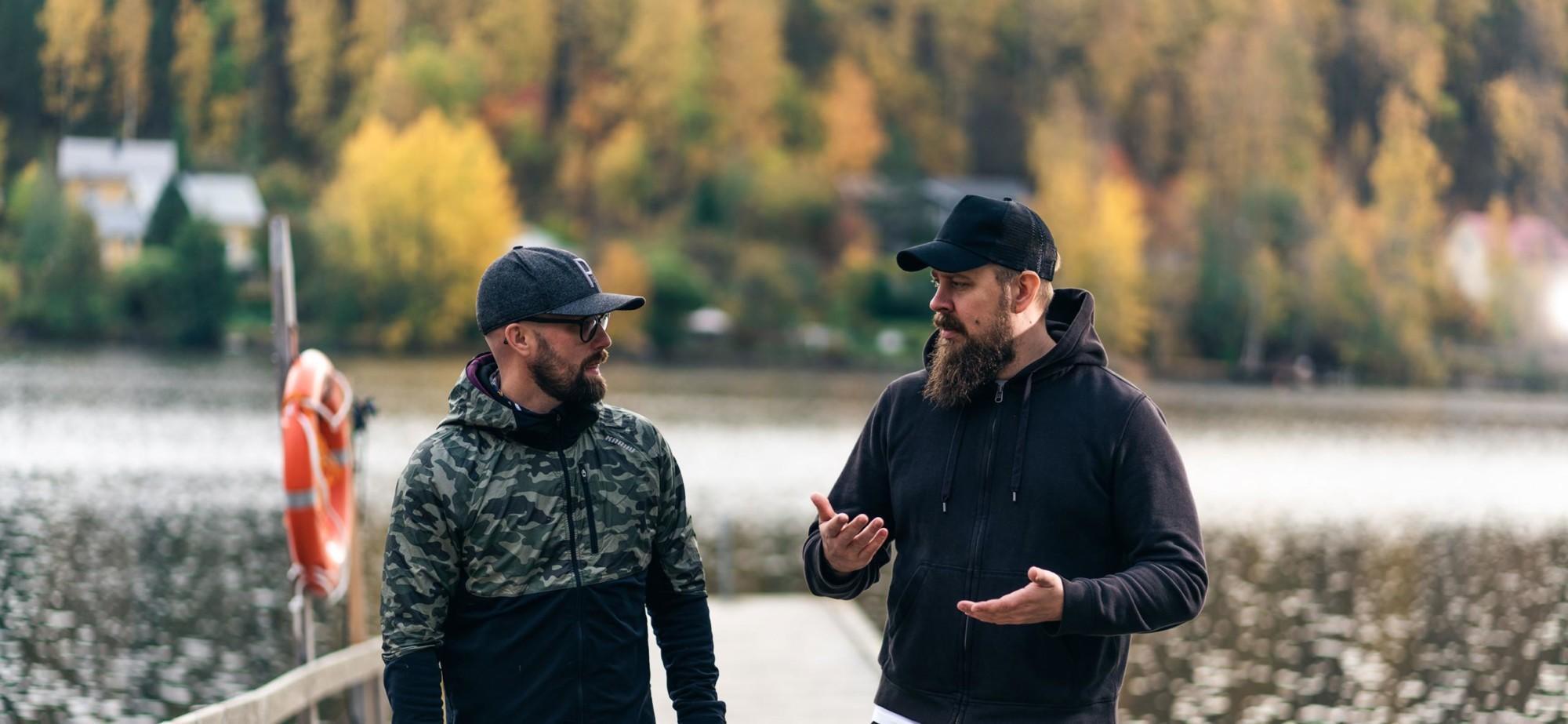 Kaksi miestä seisoo laiturilla keskustelemassa.