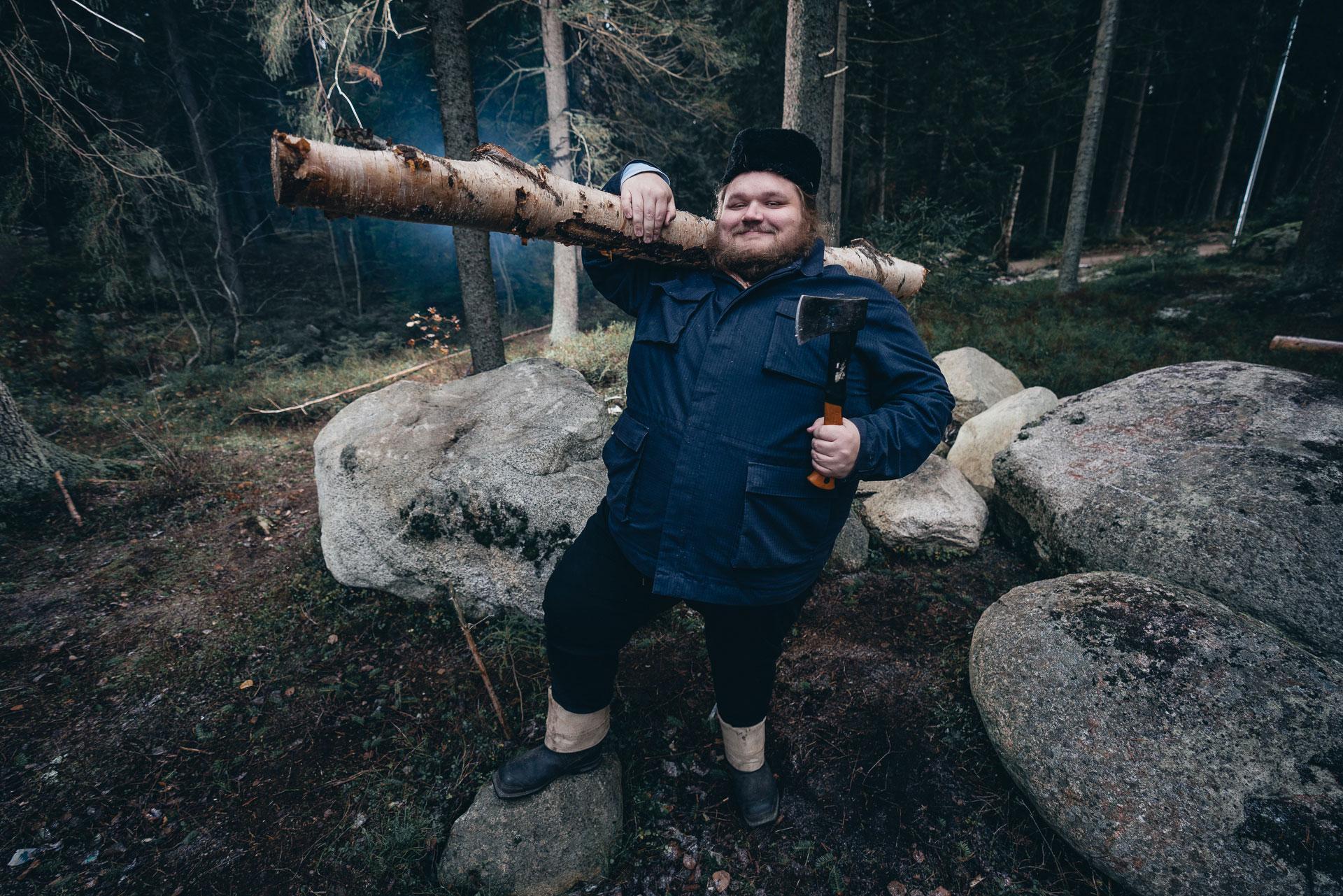Mies kantaa koivupölliä ja kirvestä toisessa kädessään.