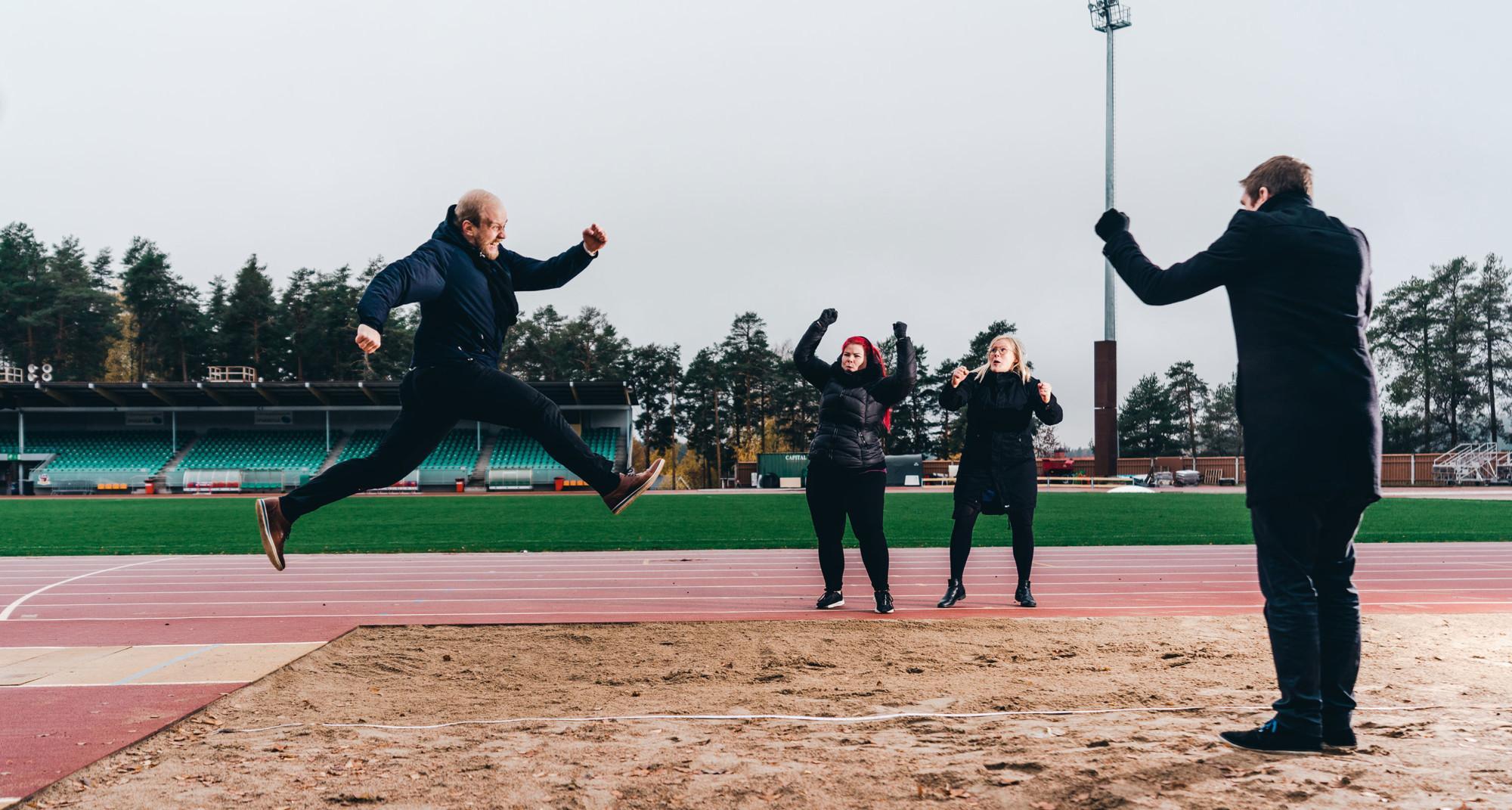 Yksi hyppää pituushyppyä ja kolme muuta ihmistä kannustaa.