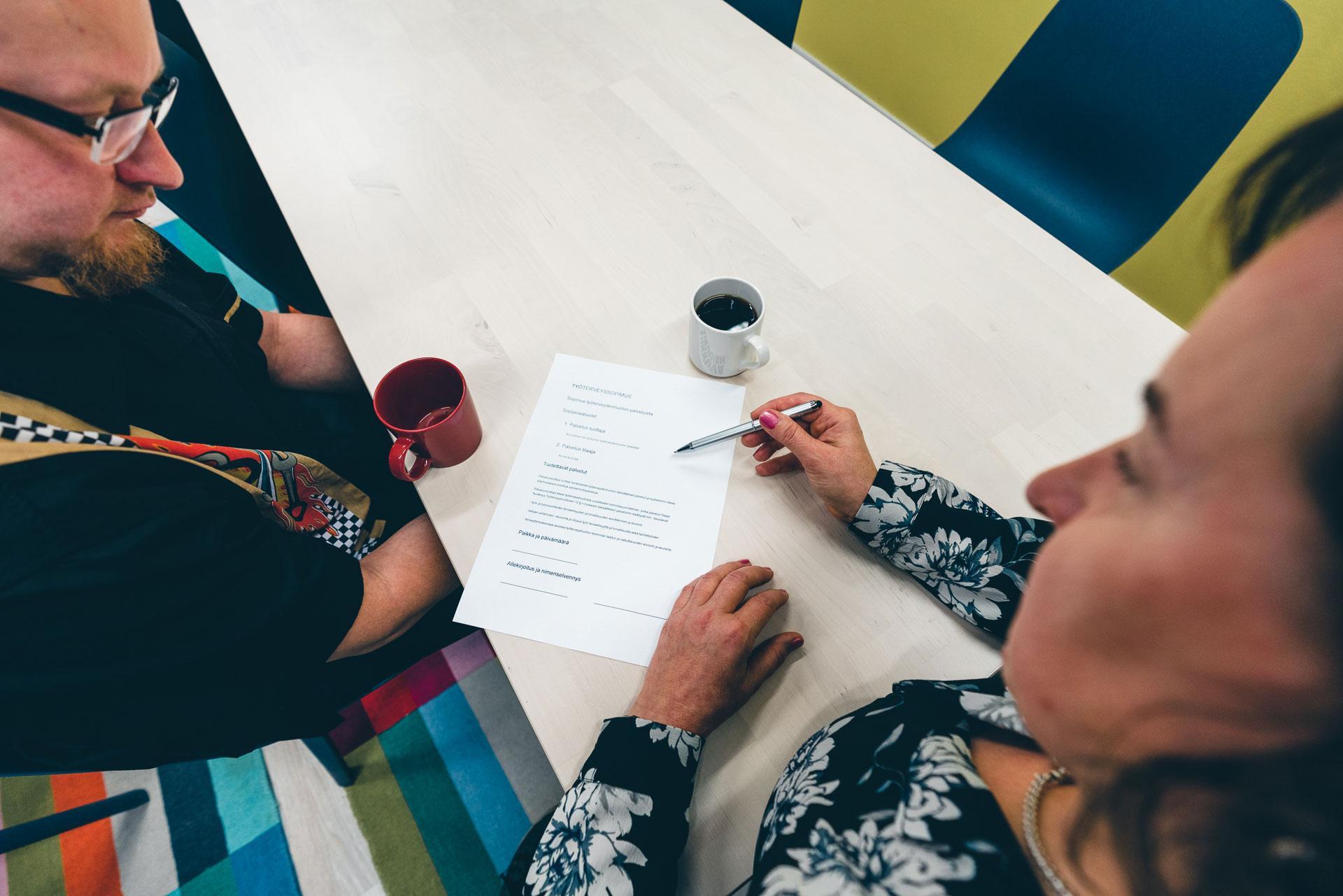 Nainen ja mies istuvat pöydän äärellä ja katselevat yhdessä edessään olevaa lomaketta.