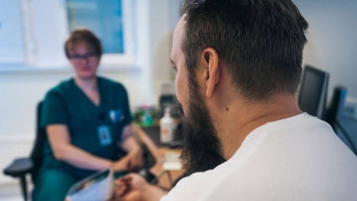 Kuvassa on taustalla hoitohenkilökuntaa edustava nainen ja etualalla mies selin kameraan päin. Henkilöt istuvat pöydän ääressä, mahdollisesti lääkärin vastaanotolla.