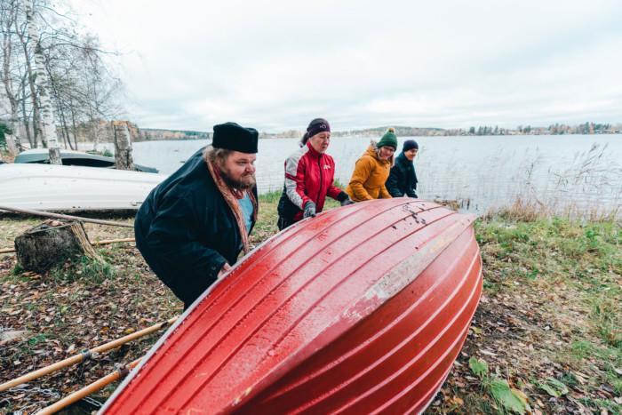 Kuvassa kaksi naista ja kaksi miestä kääntävät punaista soutuvenettä oikein päin syksyisellä rannalla.